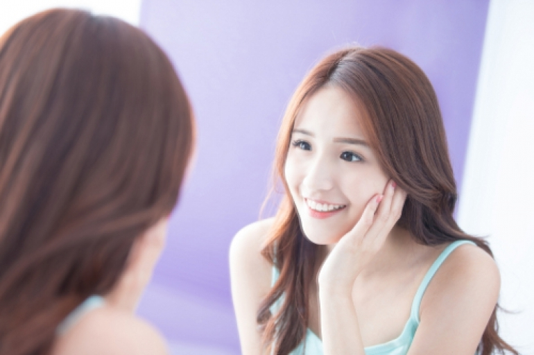 笑顔で鏡にうつる女性