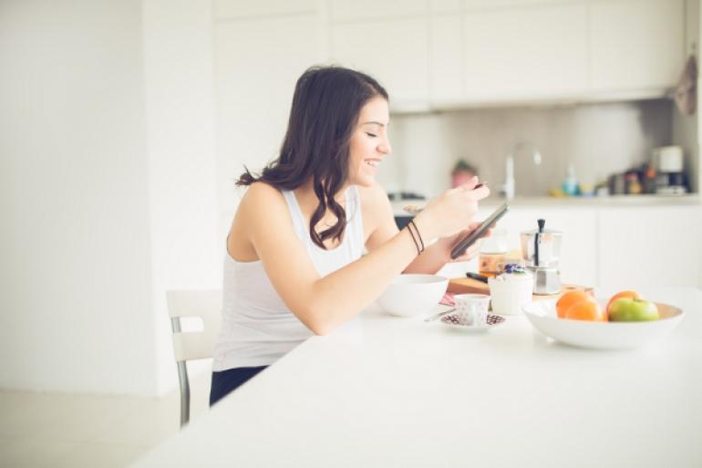 ひとりで食事しながらスマホを見て笑う女性