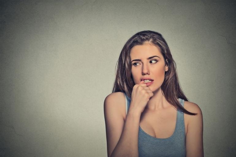 爪を噛む女性